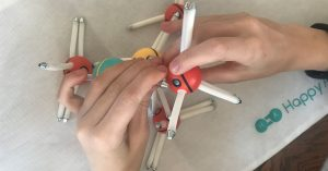 "image of teen using ""Happy Atoms"" model building kit"